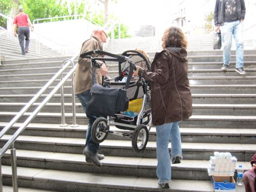 carrying-baby-stroller-upstairs