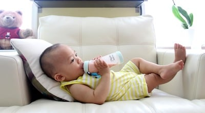 Baby drinking milk from Playtex bottle